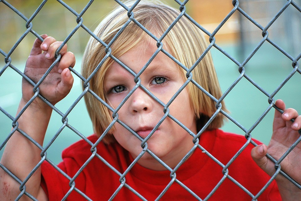 Boy Behind Fence